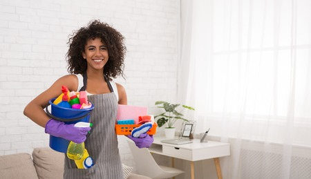 Smiling african-american woman posing with cleaning supplies, housewife preparing detergents for housecleaning, copy space