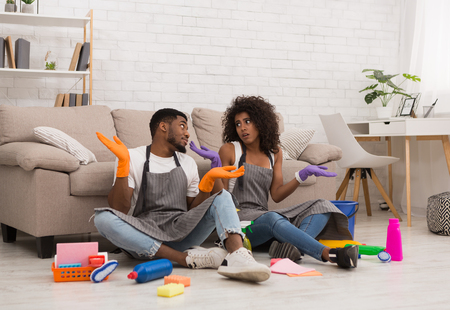Doubtful african-american couple sitting on floor before cleaning house with lots of tools, copy space Reklamní fotografie