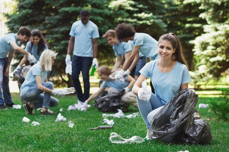 Happy woman volunteer cleaning park with friends, copy space