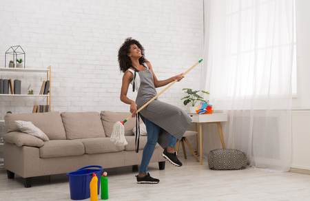Happy african-american woman dancing with mop like guitar player, having fun during spring cleaning