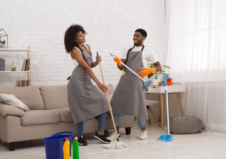 Young african-american couple cleaning home, playing with mop and broom, having fun in living-room