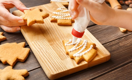 Child and mom decorating Christmas gingerbread cookies on wooden board Stock Photo