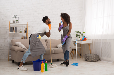 Happy african-american couple having fun, playing like singer with cleaning tool during housecleaning Stock Photo