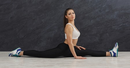 Fitness woman at stretching training, doing the splits at grey background indoors. Young slim girl makes aerobics exercise, copy space