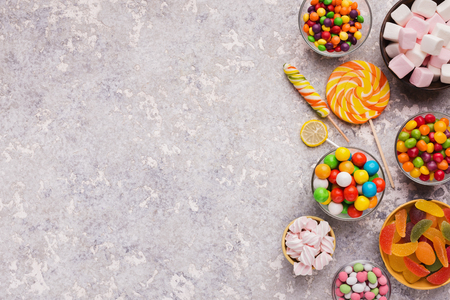 Different candies border on light textured background, copy space Stock Photo