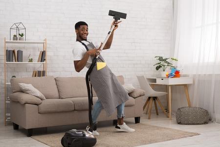 Joyful house cleaning. Cheerful african-american man having fun with vacuum cleaner, dancing like guitarist Stock Photo