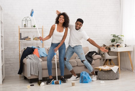 Young african-american family cleaning apartment after house party, being in good mood Stock Photo