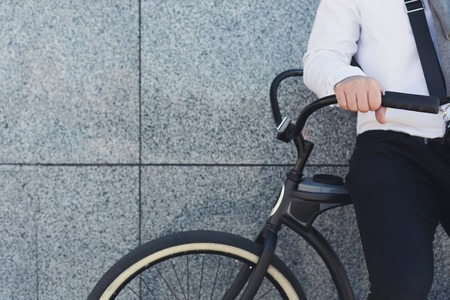 Elegant style. Close-up of unrecognizable businessman standing near his bicycle against grey background, copy space Stock Photo