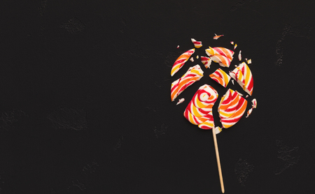 Big colorful lollipop candycrashed in pieces, black backgroun, copy space