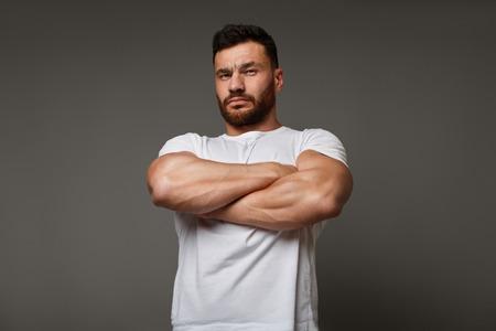 Spierconcept - verdachte jongeman met gekruiste grote gespierde armen die zijn arrogante kracht en mannelijke kracht tonen, neerkijkend op de camera Stockfoto
