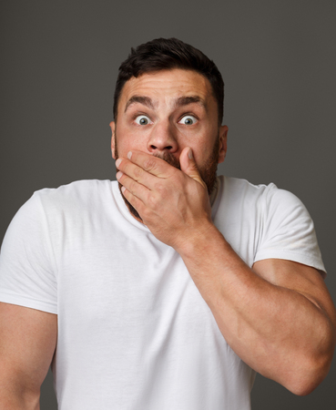 Amazed man with widely opened eyes covering his mouth over gray background