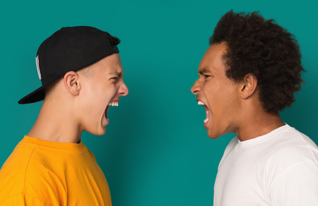 Two angry teens yelling, shouting at each other blaming for problems on blue background. Zdjęcie Seryjne - 112542846