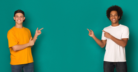 Friendly teen boys pointing on copy space over blue background