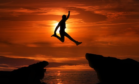 Freedom, risk, challenge and success. Man jumping over precipice between two rocky mountains at sunset. Motivational poster, copy space Stockfoto