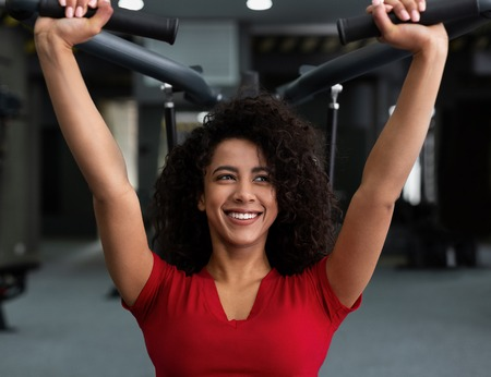 African-american woman exercising at gym, biceps workout on machine Stockfoto