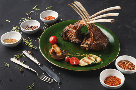 Rack of Lamb with grilled vegetables with cutlery and spices. Restaurant serving of bbq meat with mushroom, zucchini and cherry tomato, closeup Archivio Fotografico