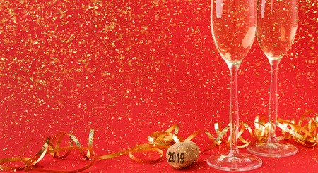 Champagne flutes and bottle cork with 2019 numbers at red holiday background with golden glitters and tinsel. Celebrating christmas, new year or birthday. Mockup for xmas postcard, crop