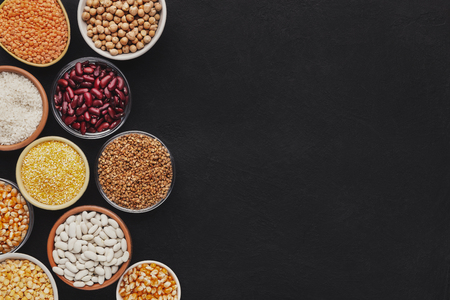 Various grains in different bowls on black background, top view, copy space Imagens