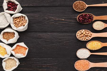 Various grains in cloth bags and spoons on wooden background, top view, copy space
