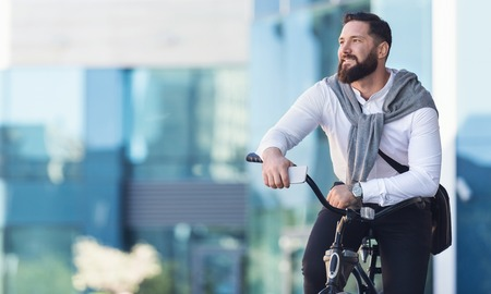Businessman leaning on bicycle, having break in riding, copy space Stock Photo