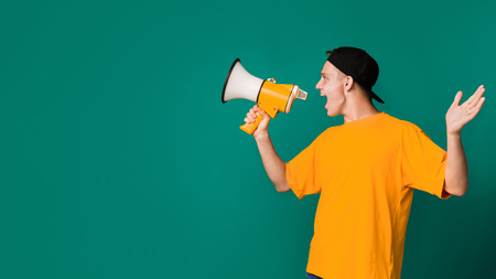 Teenager shouting using megaphone over turquoise background, copy space, side view