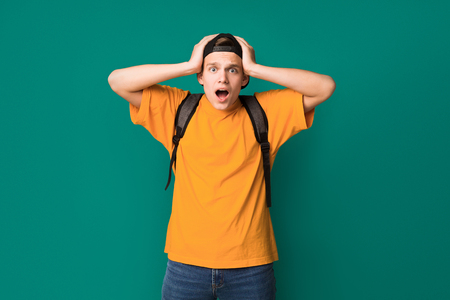 Dont believe. Surprised teen guy with hands on head over turquoise background Archivio Fotografico