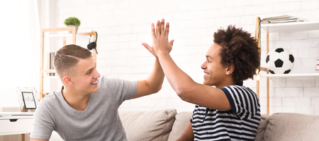 Diverse friends giving high-five while playing football game on console at home
