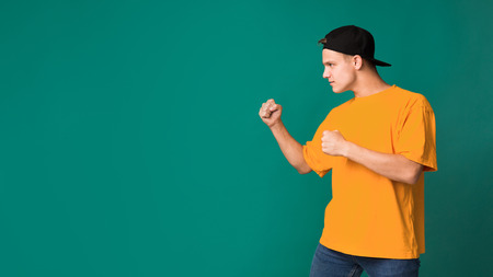 Teenager in boxing pose, clenching fists in fight gesture on turquoise background, copy space 版權商用圖片