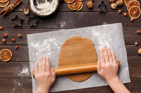 Woman cooking gingerbread cookies on Christmas eve, top view
