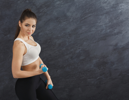 Fitness model woman with dumbbells on grey studio background, side view. Bodybuilding, healthy lifestyle concept