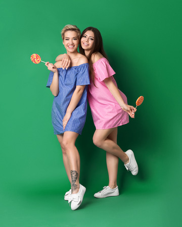 Trendy happy girls wearing mini dresses and white sneakers with lollipops on green background Banco de Imagens