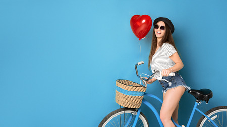 Smiling hipster girl riding bike with red heart ballon on blue background, copy space