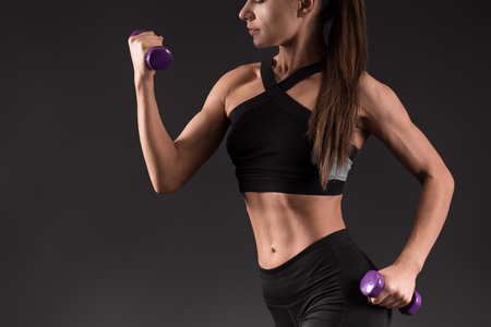 Attractive fitness woman with dumbbells . Sporty girl with well trained body training biceps on black background