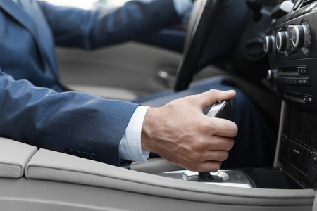 Business man hand holding gear stick levels in luxury car, closeup