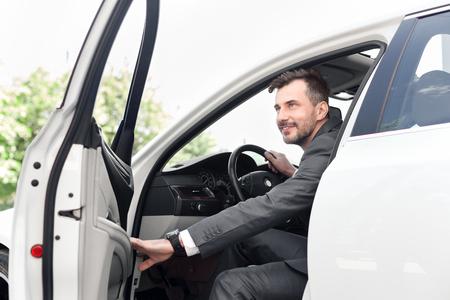 Jeune homme d'affaires assis dans sa nouvelle voiture et se rendant au bureau