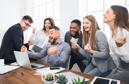 Happy businesspeople triumphing with raised fists, looking at laptop