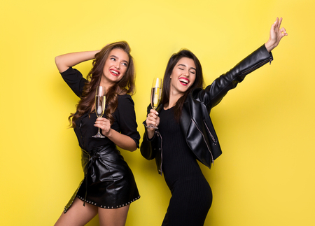 Two beautiful girls in black jackets dancing and having fun with glasses of champagne, yellow studio background 免版税图像
