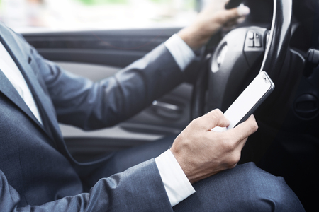 Ignoring safety. Business man texting on smartphone and driving car