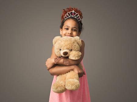 Little african-american princess girl with teddy bear Archivio Fotografico