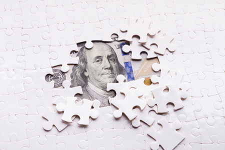 Hidden assets concept. One hundred dollar banknote appearing under puzzle pieces Standard-Bild - 113451246