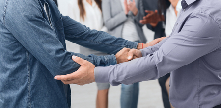 Business partners handshaking after striking deal at meeting in office
