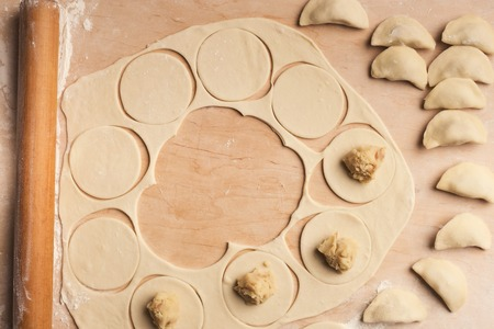Traditional Russian damplings preparation on wooden background, top view