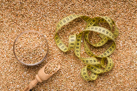 Diet and healthy eating background. Raw buckwheat with wooden spoon and measuring tape, top view