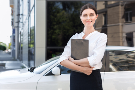Consultant girl with documents standing near new car outdoors, copy space