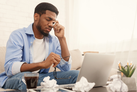Inspiration crisis. Exhausted african-american man at his working place at home, copy space Stock Photo
