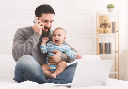 Geschäft zu Hause. Junger Vater, der am Handy spricht und neugeborenes Kind stillt, Kopienraum