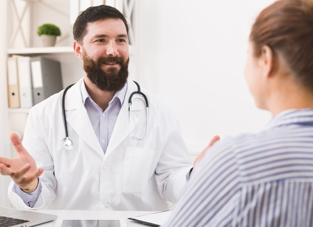 Smiling doctor talking to healthy woman patient in office, telling good news