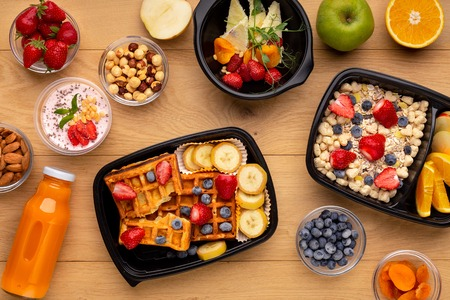 Organic breakfast meal delivery in plastic containers, top view