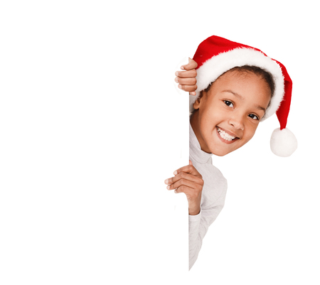 African-american girl peeking over blank board, wearing santa hat, isolated on white background 版權商用圖片