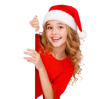 Girl in santa hat, posing behind white banner isolated on white background